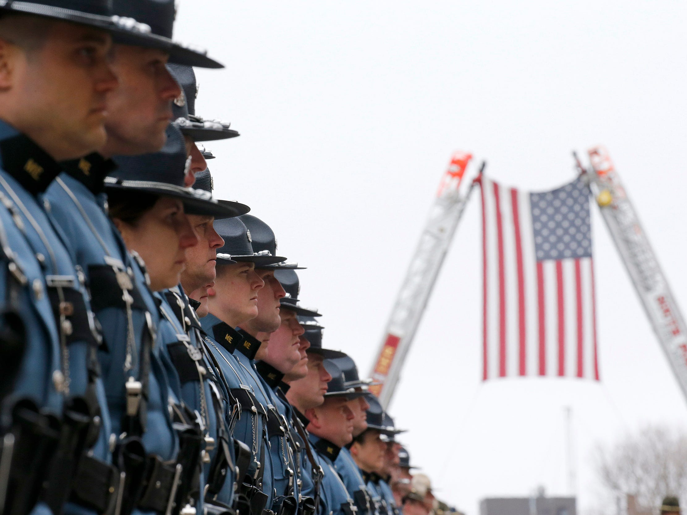 Members of the Maine State Police stand during the funeral procession for Maine State Police detective Ben Campbell Tuesday, April 9, 2019, in Portland, Maine.  Campbell was helping a motorist last week when he was struck and killed by a wheel that had dislodged from a logging truck.