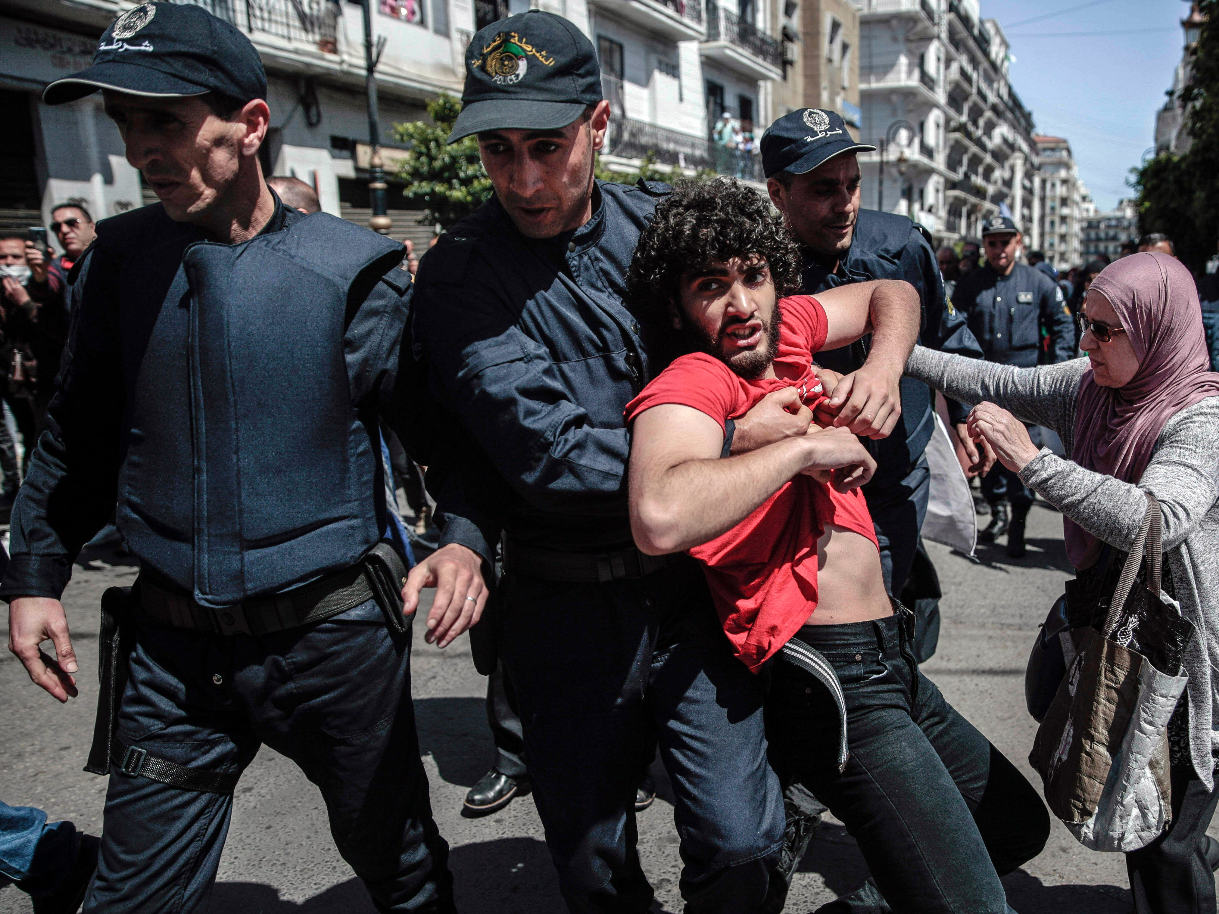 Police arrest a man as they attempt to disperse a demonstration for students in Algiers, Algeria, Tuesday, April 9, 2019. Algerian police used pepper spray and a water cannon to break up a group of students protesting in the country's capital, less than an hour after the country's parliament chose an interim leader.