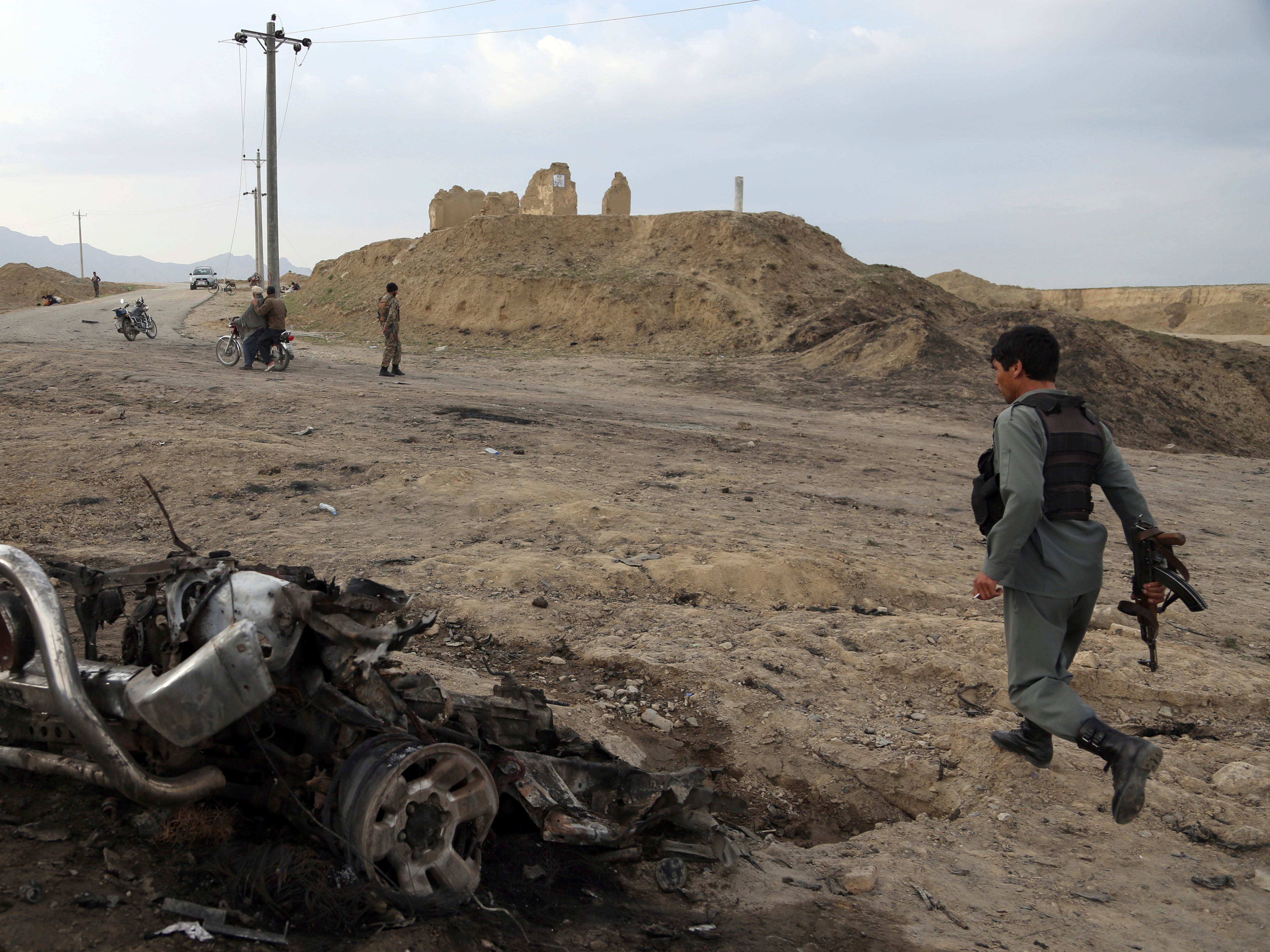 Afghan security forces gather at the site of Monday's attack near the Bagram Air Base, north of Kabul, Afghanistan, Tuesday, April 9, 2019. Three American service members and a U.S. contractor were killed when their convoy hit a roadside bomb near the main U.S. base in Afghanistan, the U.S. forces said. The Taliban claimed responsibility.