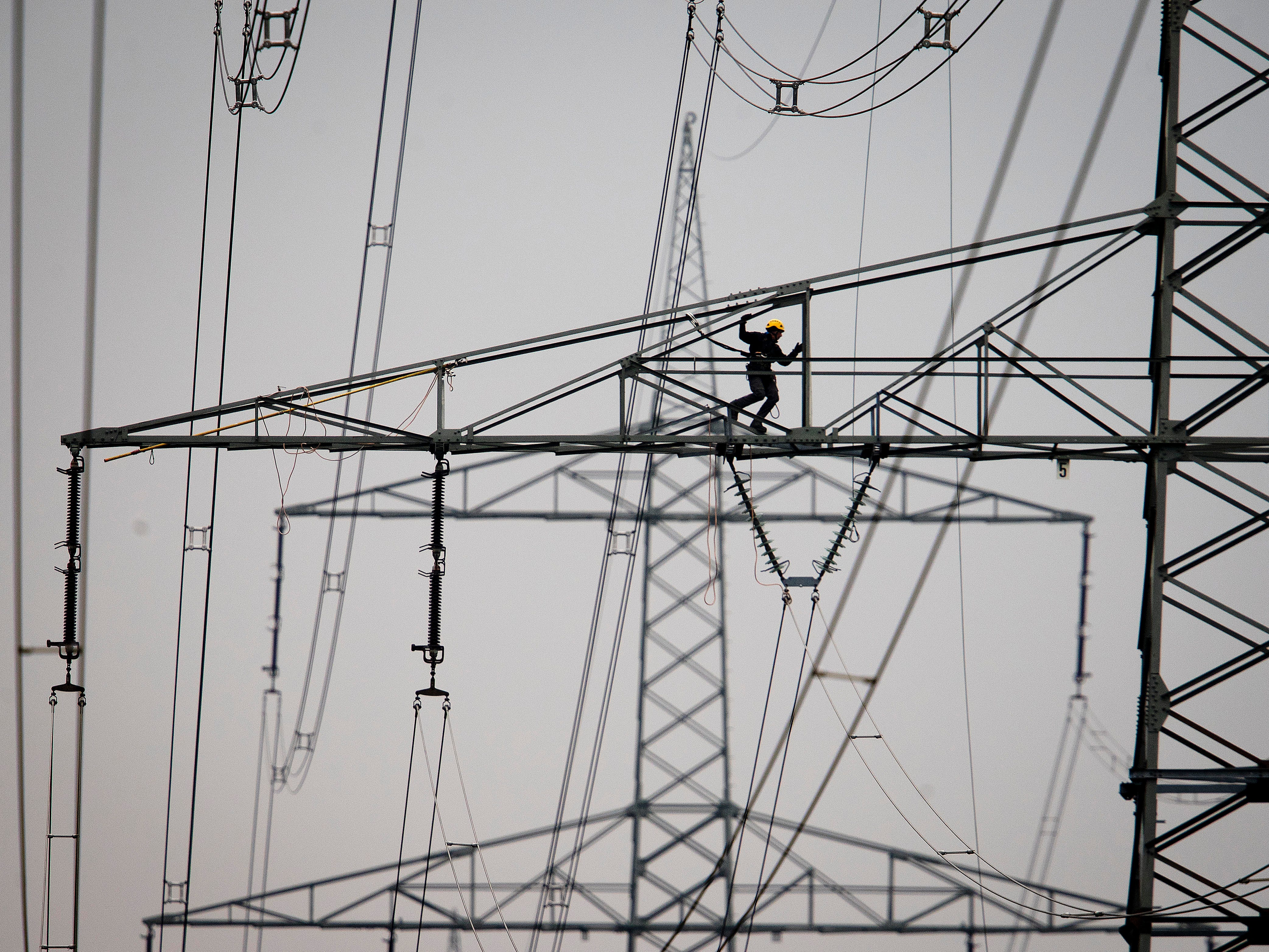 A technician works on high-voltage pylons in Frankfurt, Germany, Tuesday, April 9, 2019.