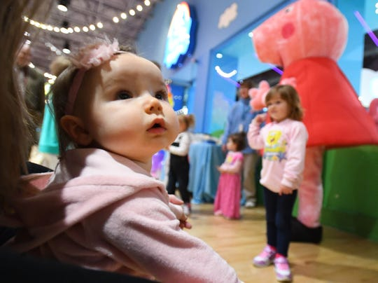 Athena Schafer, 10 months, with mother Christina Schafer, meet Peppa and George during the grand opening of the Peppa Pig World of Play on Tuesday at Great Lakes Crossing.