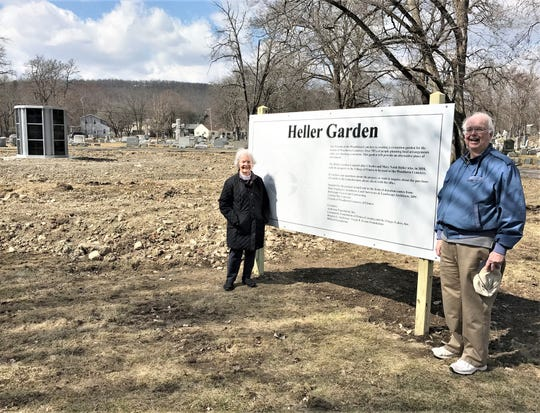 Jim Hare, board member of Friends of Woodlawn Cemetery, and Suzy Heller Smith stand next to a sign that honors Heller Smith's great grandparents, who sold the land for the cemetery to the City of Elmira in 1858.