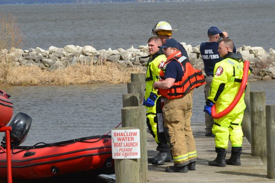 Crews stand near an inflatable boat on Lake Winnebago during a water rescue. A kayaker was stranded a mile from shore after overturning.