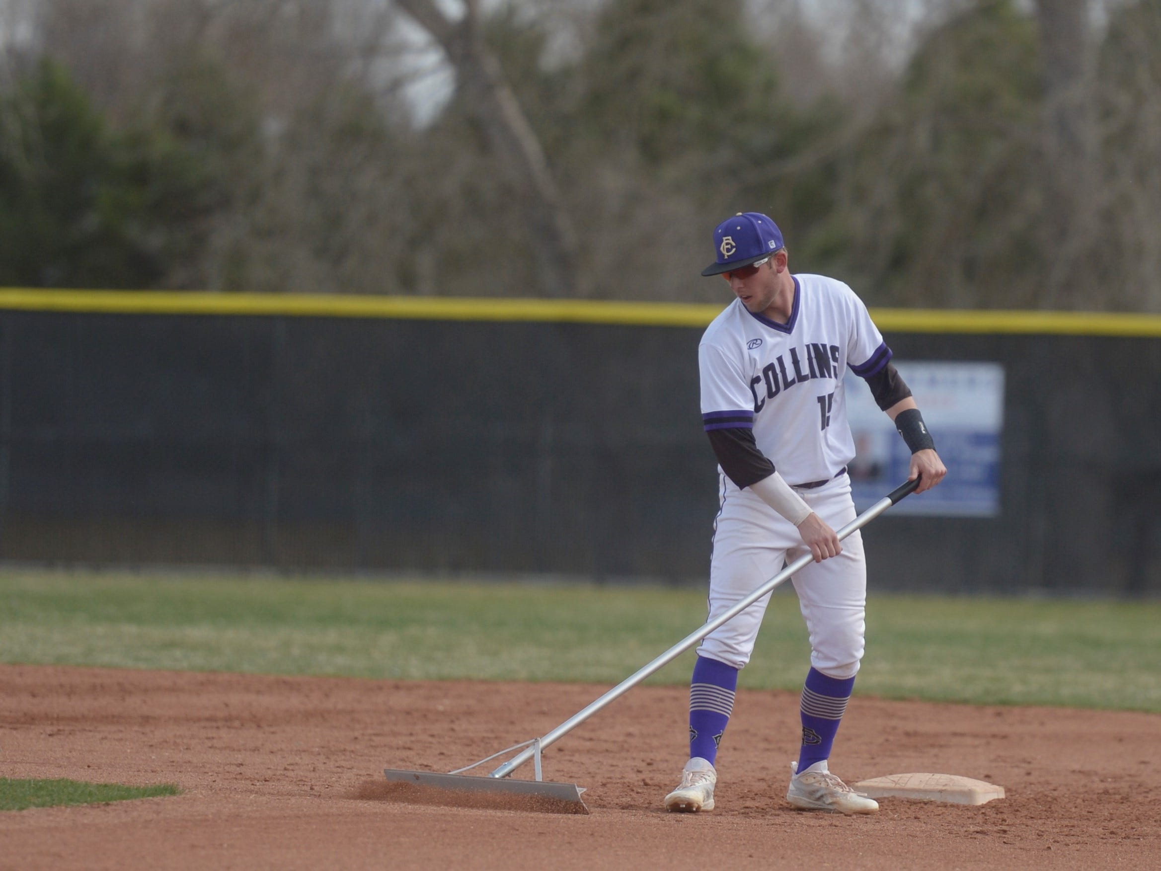Fort Collins High School baseball player Caleb Brlecic rakes the dirt before a game against Denver South on Monday, April 8, 2019. The Lambkins won 13-3 to move to 10-0 on the season.