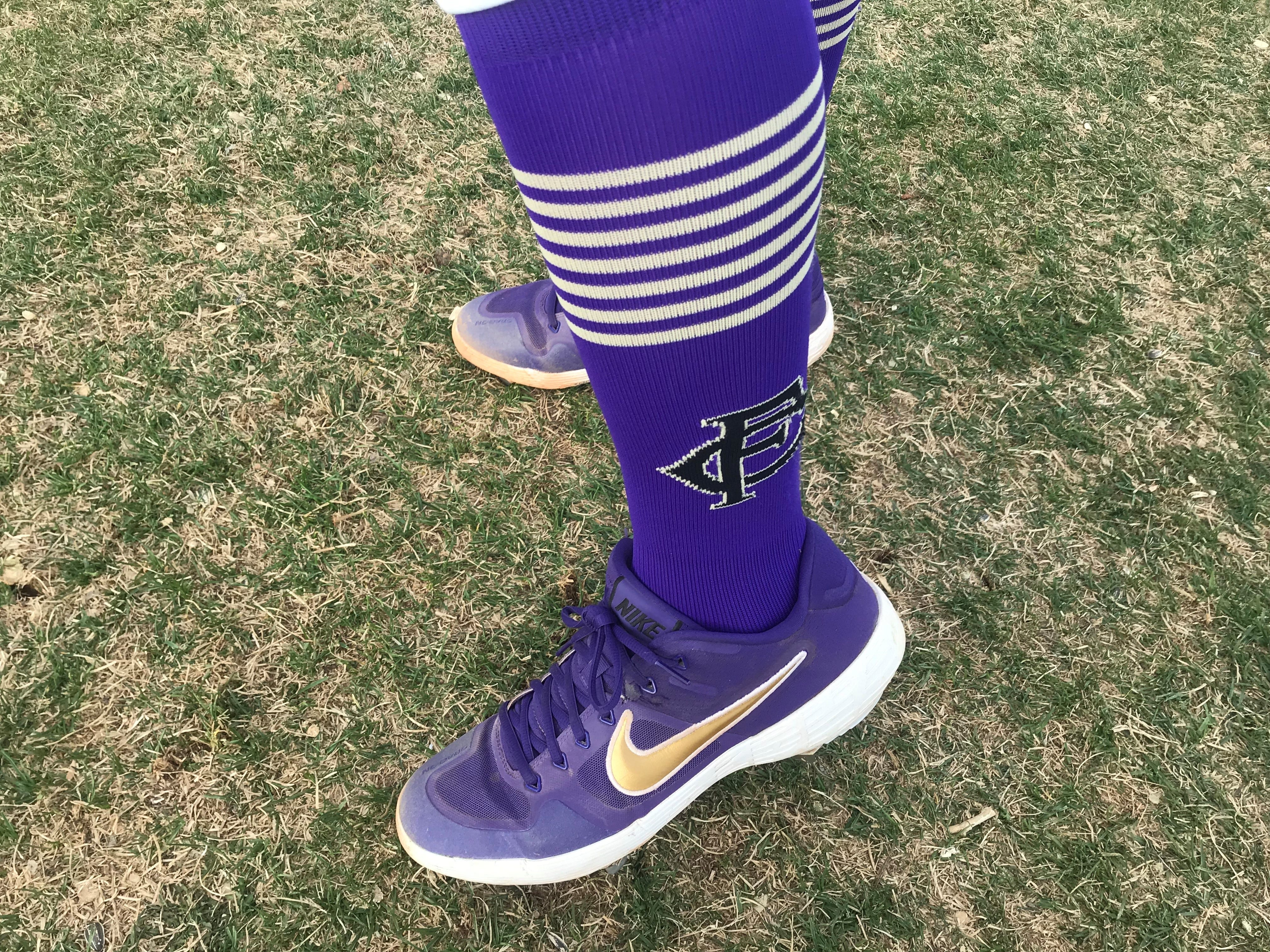 Fort Collins High School catcher Diego Aragon shows off the high socks worn by the whole Lambkins team plus the custom cleats many of the players wear.
