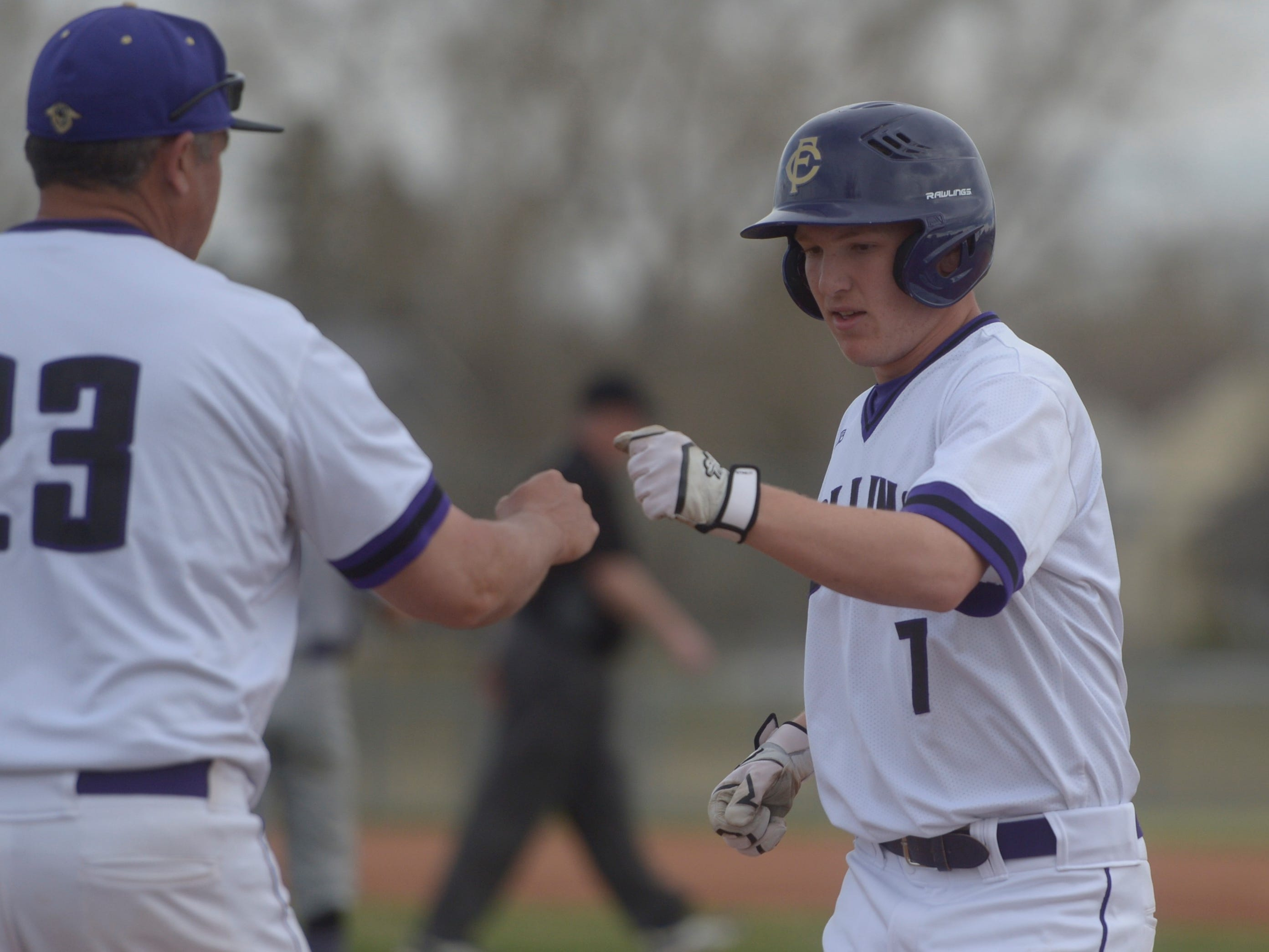 Fort Collins High School outfielder Drew Norsen fist-bumps assistant coach Keith Aragon after a base hit during a game against Denver South on Monday, April 8, 2019. The Lambkins won 13-3 to move to 10-0 on the season.