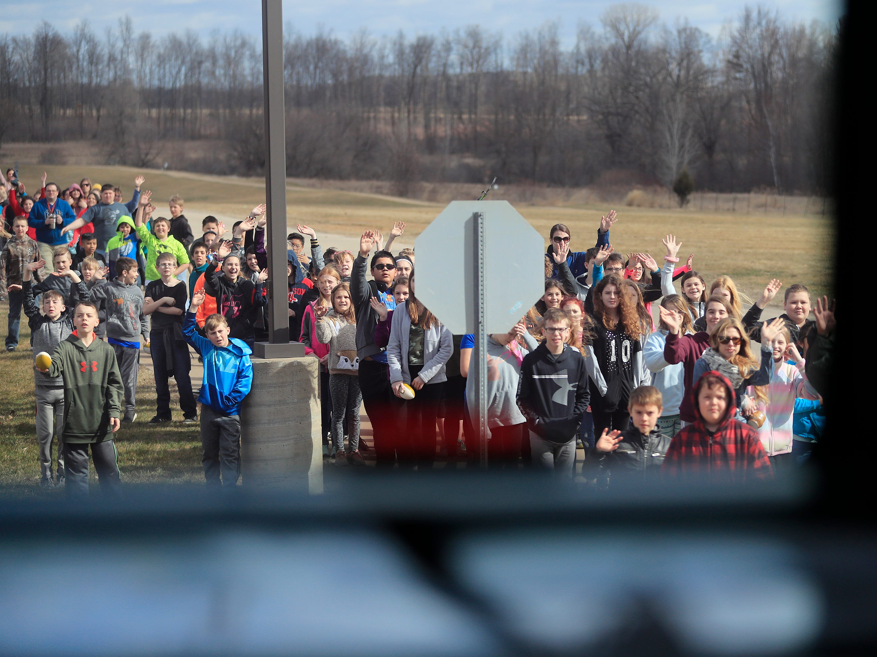 Students wave as the Green Bay Packers bus departs from a stop on the Packers Tailgate Tour at Clintonville High School on Tuesday, April 9, 2019 in Clintonville, Wis.