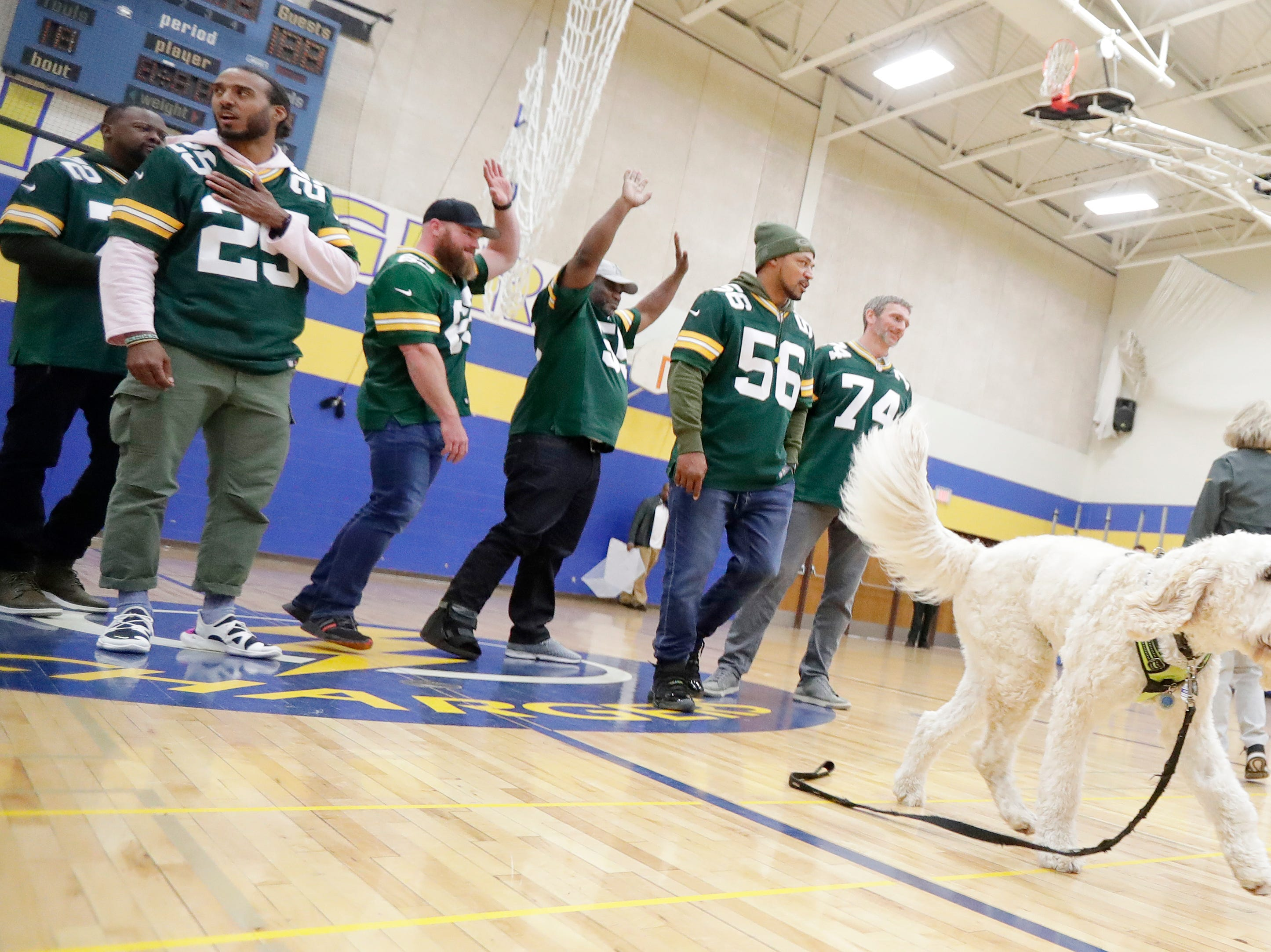 Former Green Bay Packers players wave to the crowd after posing with Henry, the school therapy dog, during a stop on the Packers Tailgate Tour at Ben Franklin Junior High High School on Tuesday, April 9, 2019 in Stevens Point, Wis.