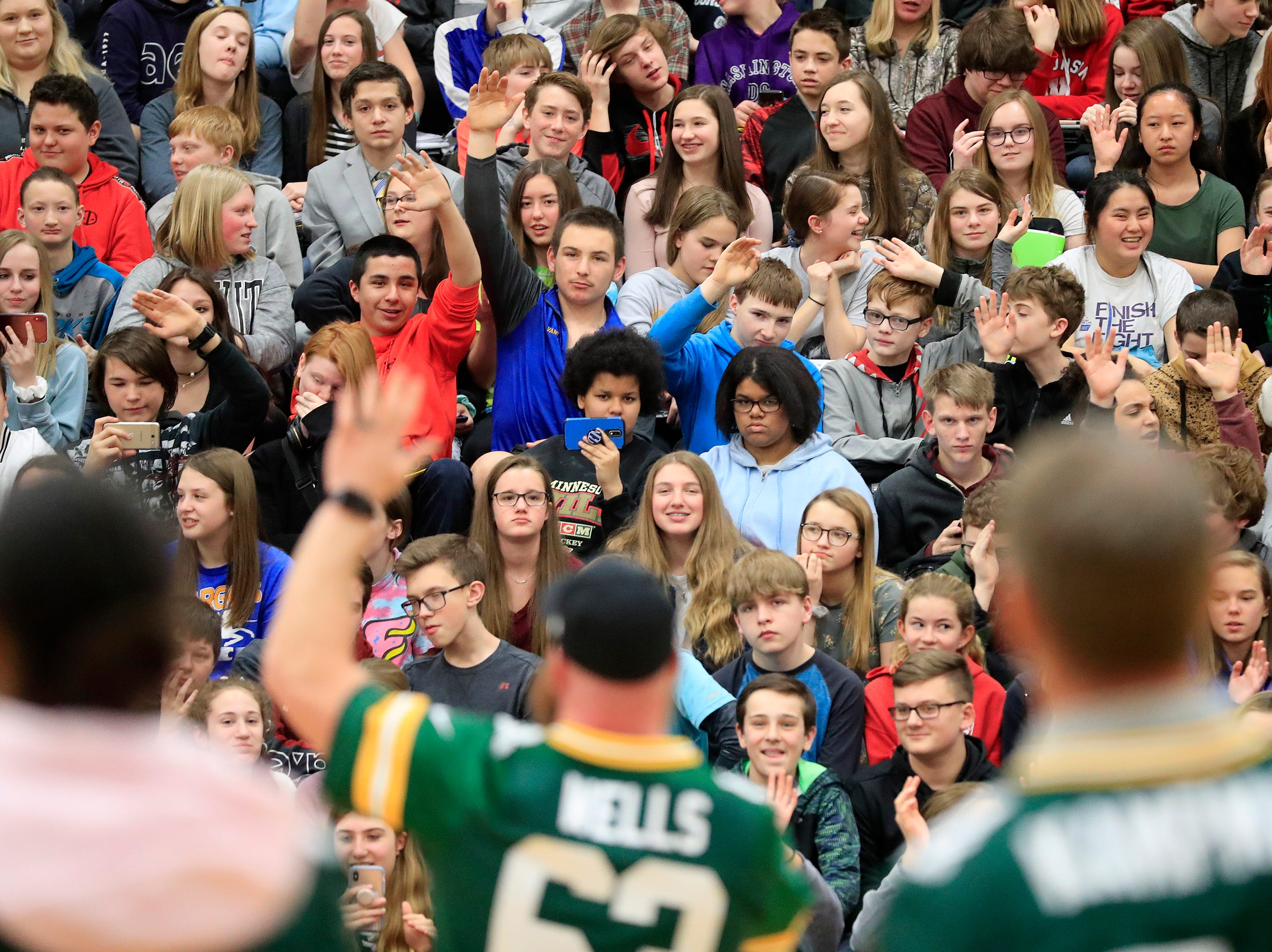Students raise their hands during a stop on the Packers Tailgate Tour at Ben Franklin Junior High School on Tuesday, April 9, 2019 in Stevens Point, Wis.