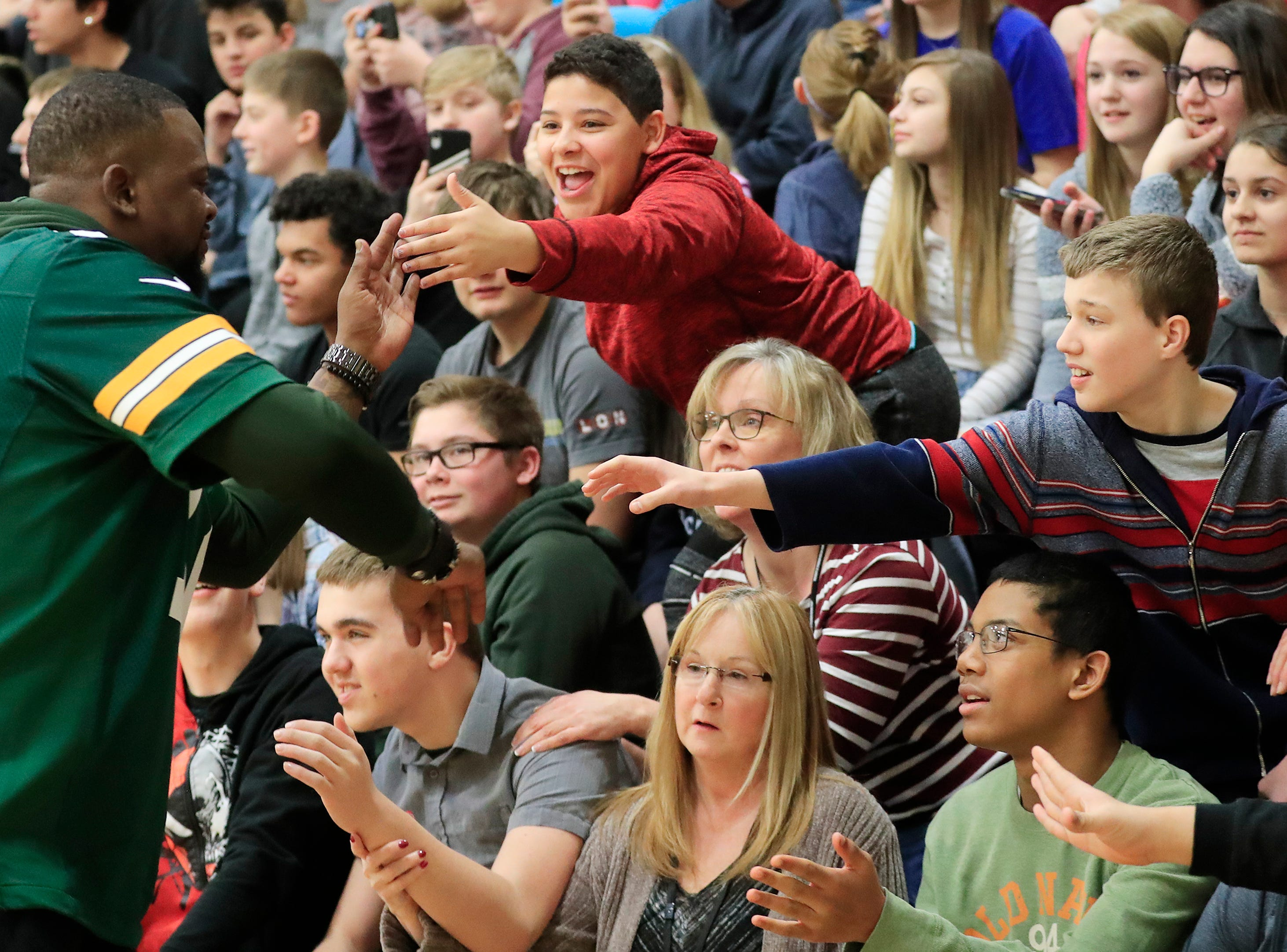 Former Green Bay Packers player Earl Dotson high fives kids during a stop on the Packers Tailgate Tour at Ben Franklin Junior High School on Tuesday, April 9, 2019 in Stevens Point, Wis.