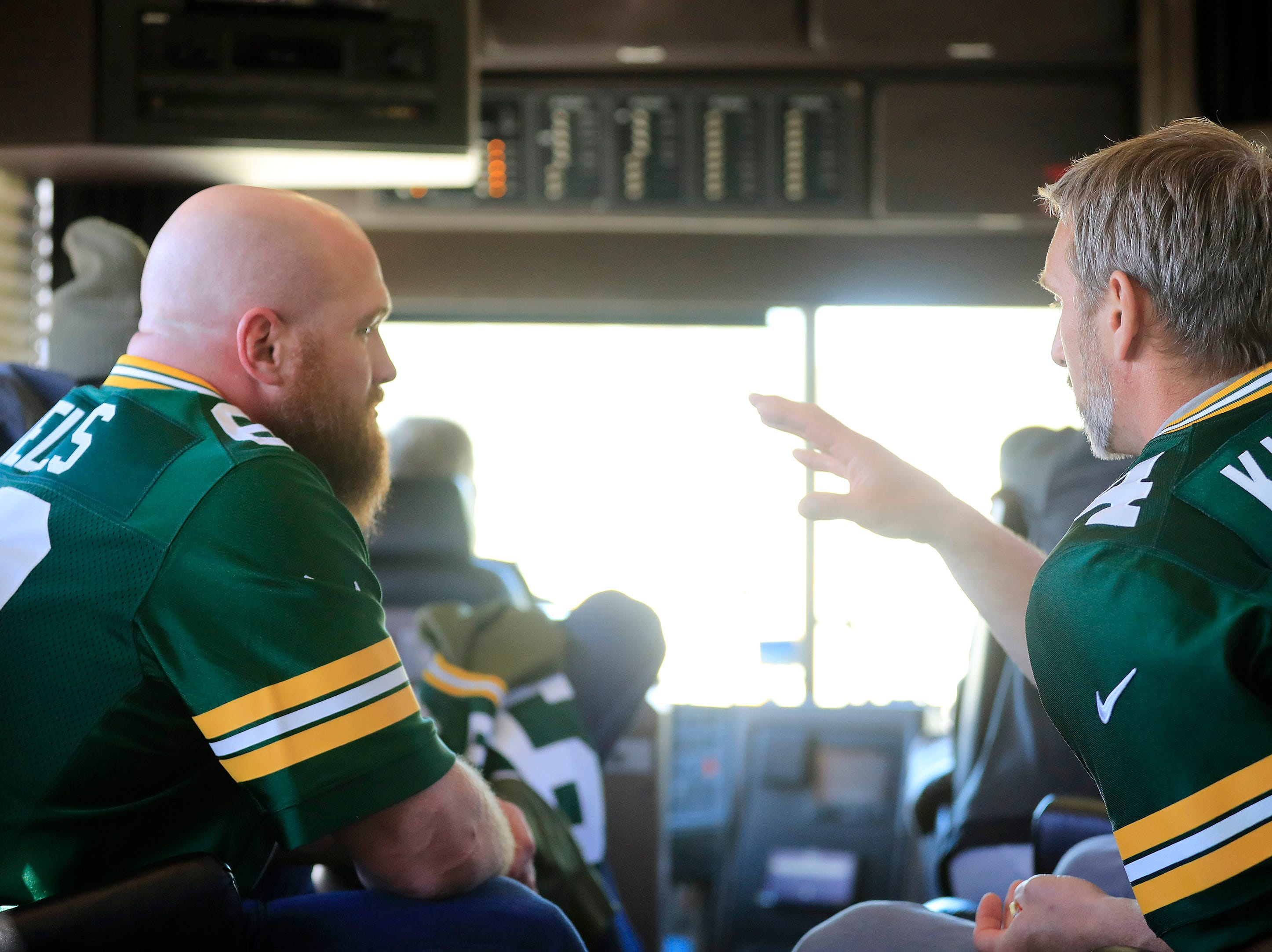 Scott Wells (left) and Aaron Kampman talk on the bus in between stops on the Packers Tailgate Tour on Tuesday, April 9, 2019 in Clintonville, Wis.