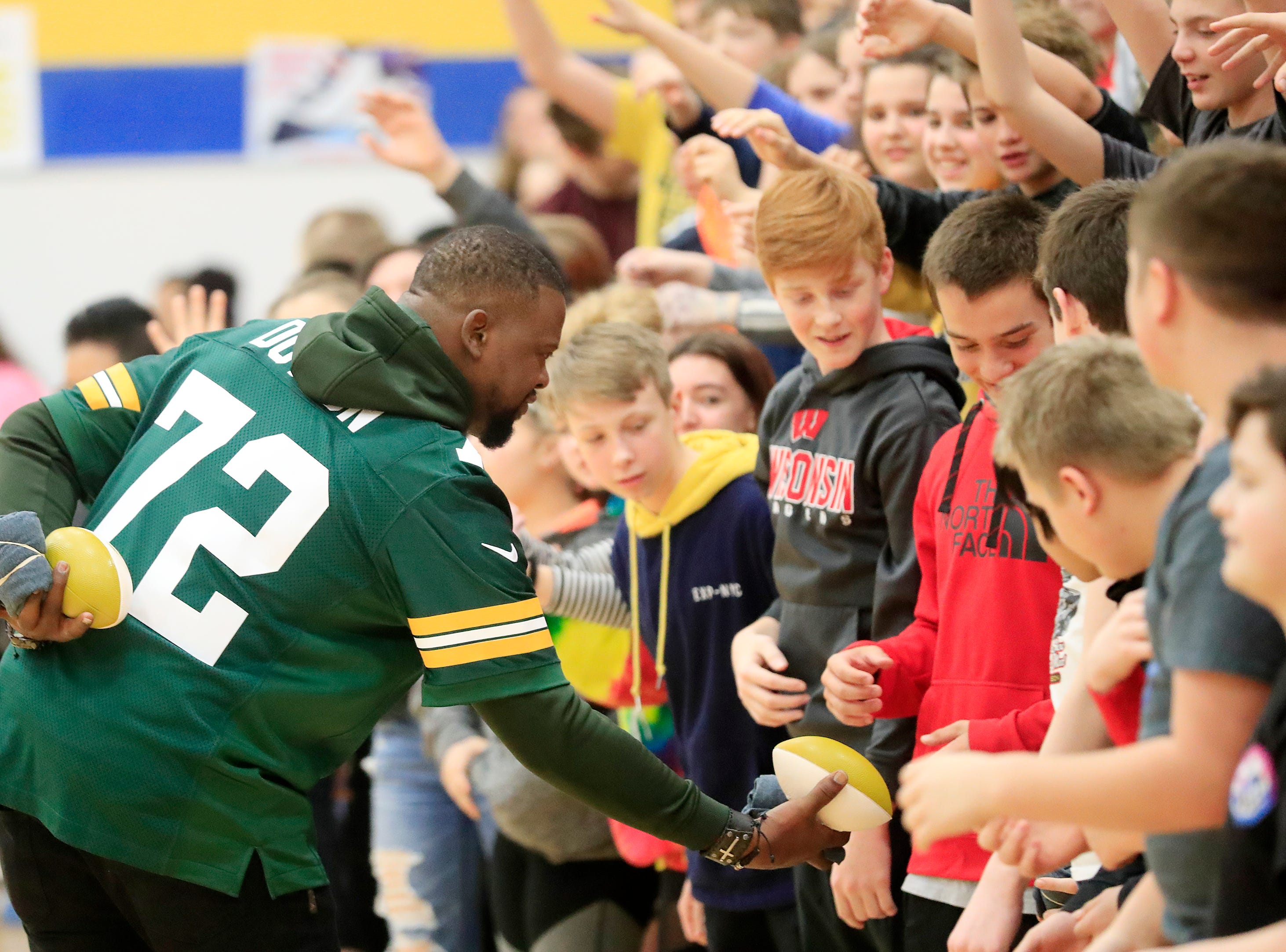 Former Green Bay Packers player Earl Dotson hands out mini footballs during a stop on the Packers Tailgate Tour at Ben Franklin Junior High School on Tuesday, April 9, 2019 in Stevens Point, Wis.