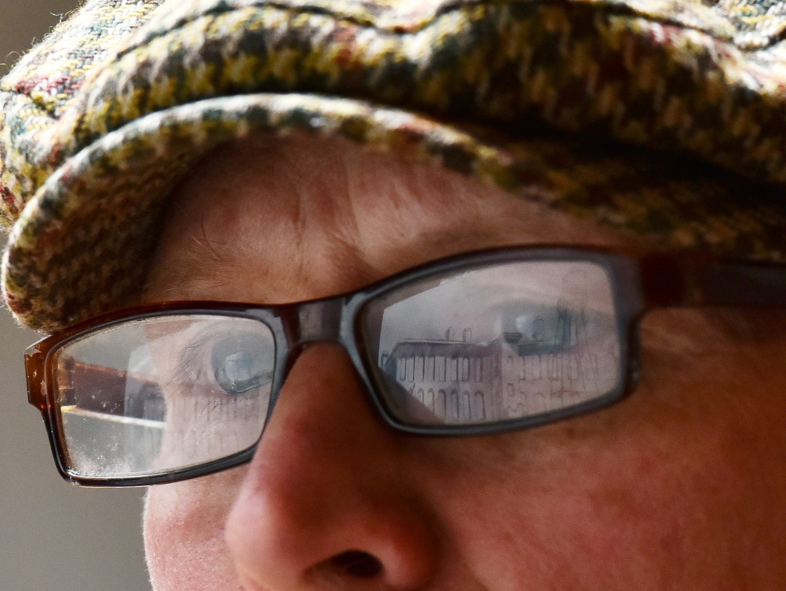 A painting is reflected in the glasses of Mark Mulfinger as he works at Railside Studios.