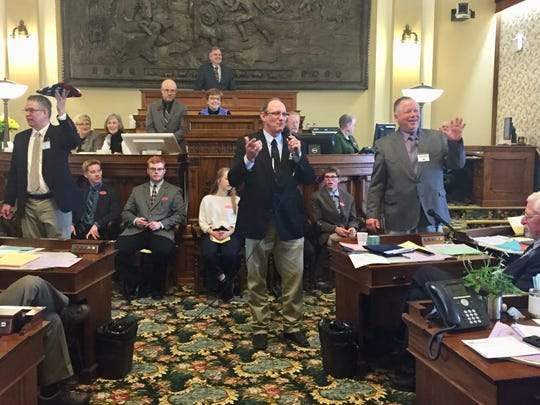 Auctioneers Kevin Hill, center, J.K. Kinsey left and Shane Ophus lead the flag bidding Tuesday on the Senate floor to help Jack Racicot, a Senate staffer.