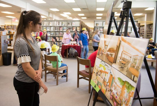 Reagan Abbott admires the renderings of the new Henderson County Public Library $8 million addition and renovation after a groundbreaking Tuesday, April 9, 2019.