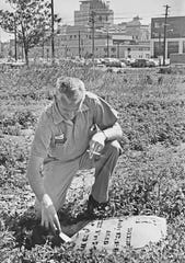 Floyd Ingram examines of several headstones found at a Diamond Chain construction site on May 18, 1967. The area was part of the former Greenlawn Cemetery.