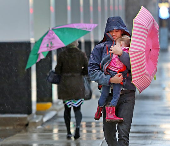 Elliott Lushin walks his sleeping 2-year-old daughter Zoey on Delaware Street in Downtown Indianapolis on a rainy and windy morning on March 20, 2017. Conditions like these are expected for Thursday and Friday of this week.