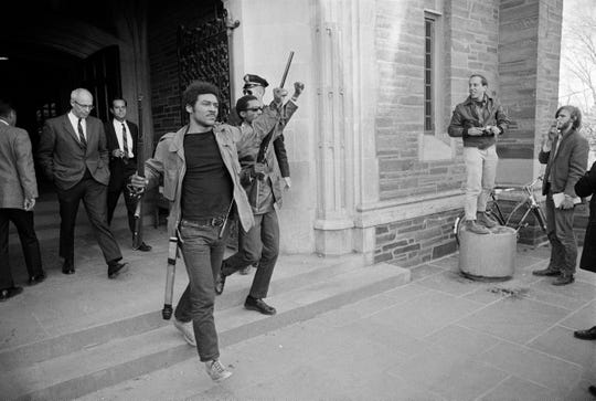 Toting a rifle and raising a clenched fist, Thomas W. Jones, spokesman for the Afro-American Society at Cornell University at Ithaca, N.Y., marches out of a student union hall after black militants occupied the building in a showdown over race relations, April 20, 1969. (AP Photo/Steve Starr)