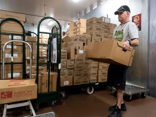 Mark Lamb of Second Harvest collects donated meats from a cooler at the Kroger Marketplace on Emory Road on Tuesday, April 9, 2019. Kroger is working to eliminate both hunger and food waste through an initiative called Zero Hunger Zero Waste and is donating foodstuffs to organizations like Second Harvest.