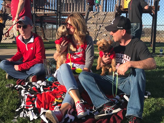 Trish LaPaille, middle, enjoys the Louisville Cardinals Bark at the Park day Tuesday with her husband, Tommy, right, son, Gavin, and dogs, Gia and Gus.