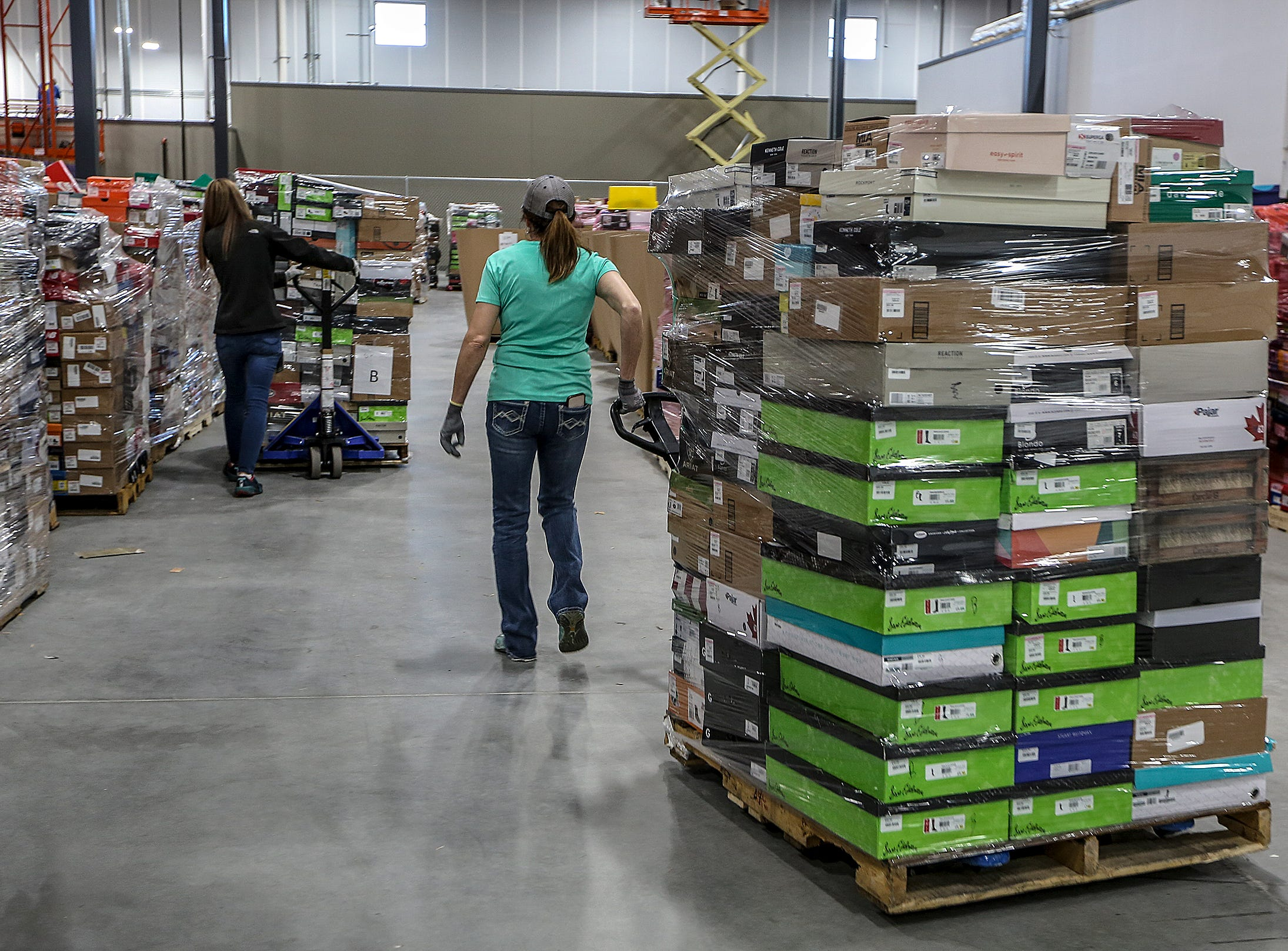 Workers unload tens of thousands of shoes are arriving at the new Zappos facility on Minors Lane.