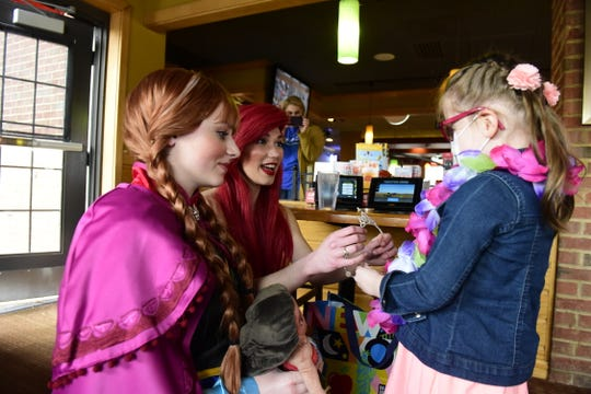 Elliana Nelson, 6, gets a tiara from two princesses Monday during her Make-A-Wish reveal party.