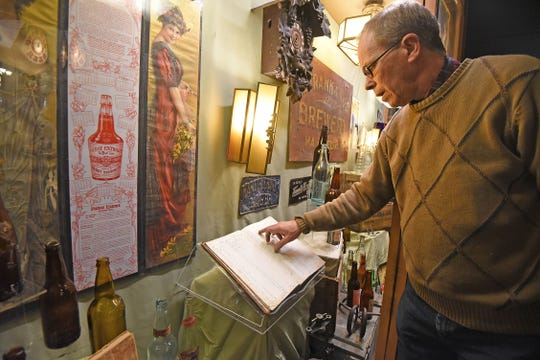 """Curator Scott Schaut reads from the only known delivery ledger from area beverage manufacturers. It is on display at the Mansfield Memorial Museum in the """"Breweries and Bottlers of Mansfield, Ohio"""" exhibit."""