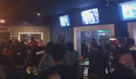 Screen shot of video with people throwing chairs and fighting at The Patio bar.
