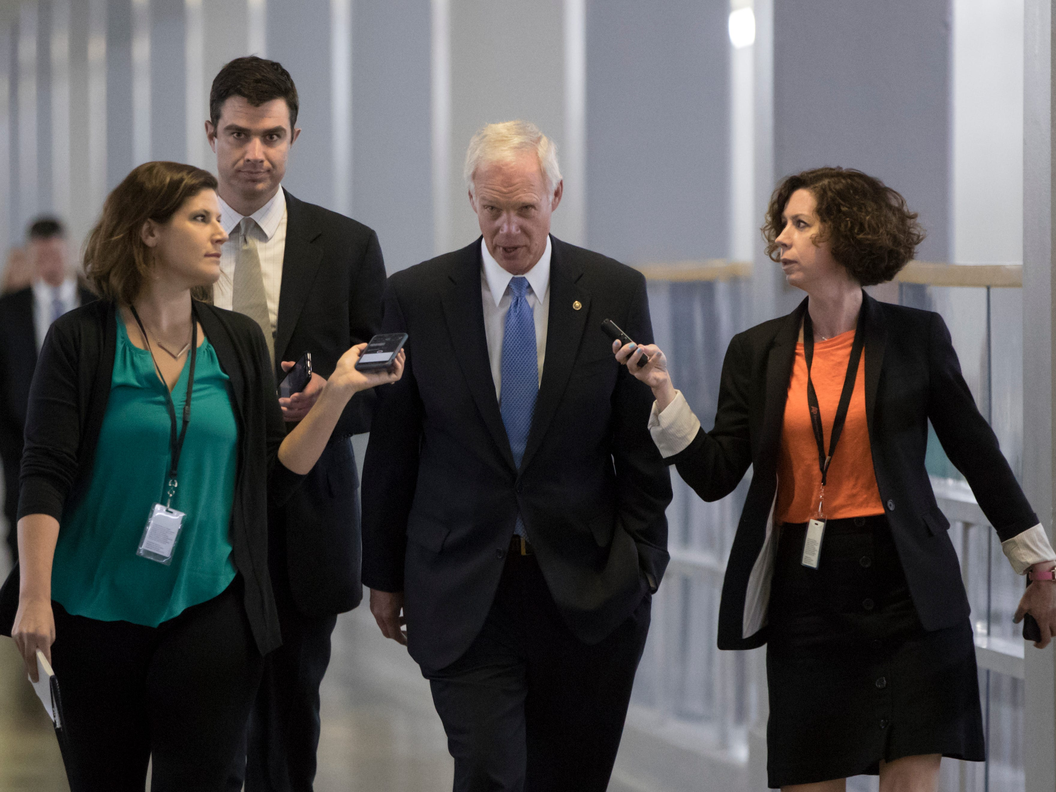 Sen. Ron Johnson, R-Wisc., center, who has expressed opposition to his own party's health care bill, walks to a policy meeting as the Senate Republican legislation teeters on the brink of collapse, at the Capitol.