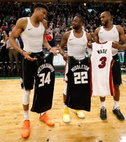 Milwaukee Bucks' Giannis Antetokounmpo, (from left), the Miami Heat's Dwyane Wade, and Khris Middleton swap jerseys with after an NBA basketball game in Milwaukee.