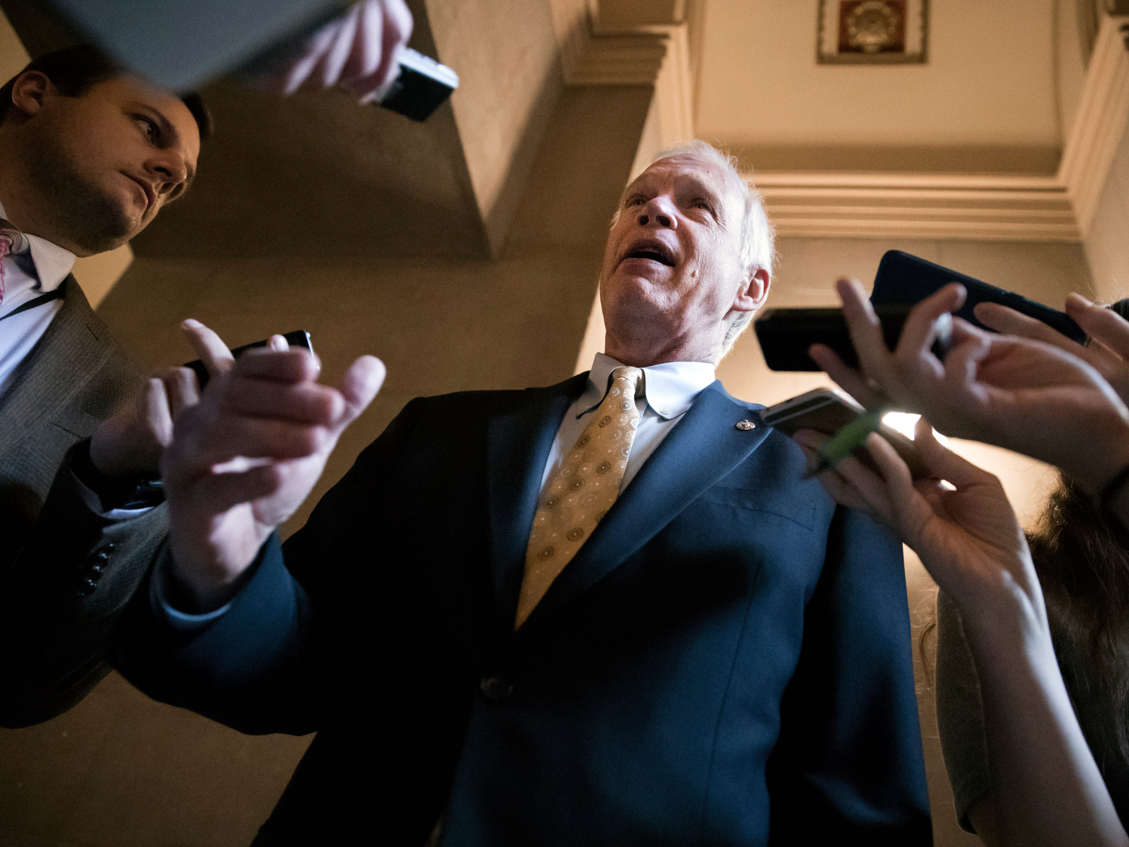 Reporters get an update from Sen. Ron Johnson, R-Wis., a member of the Senate Budget Committee, as Republican senators gather to meet with Majority Leader Mitch McConnell, R-Ky., on the GOP effort to overhaul the tax code, on Capitol Hill.