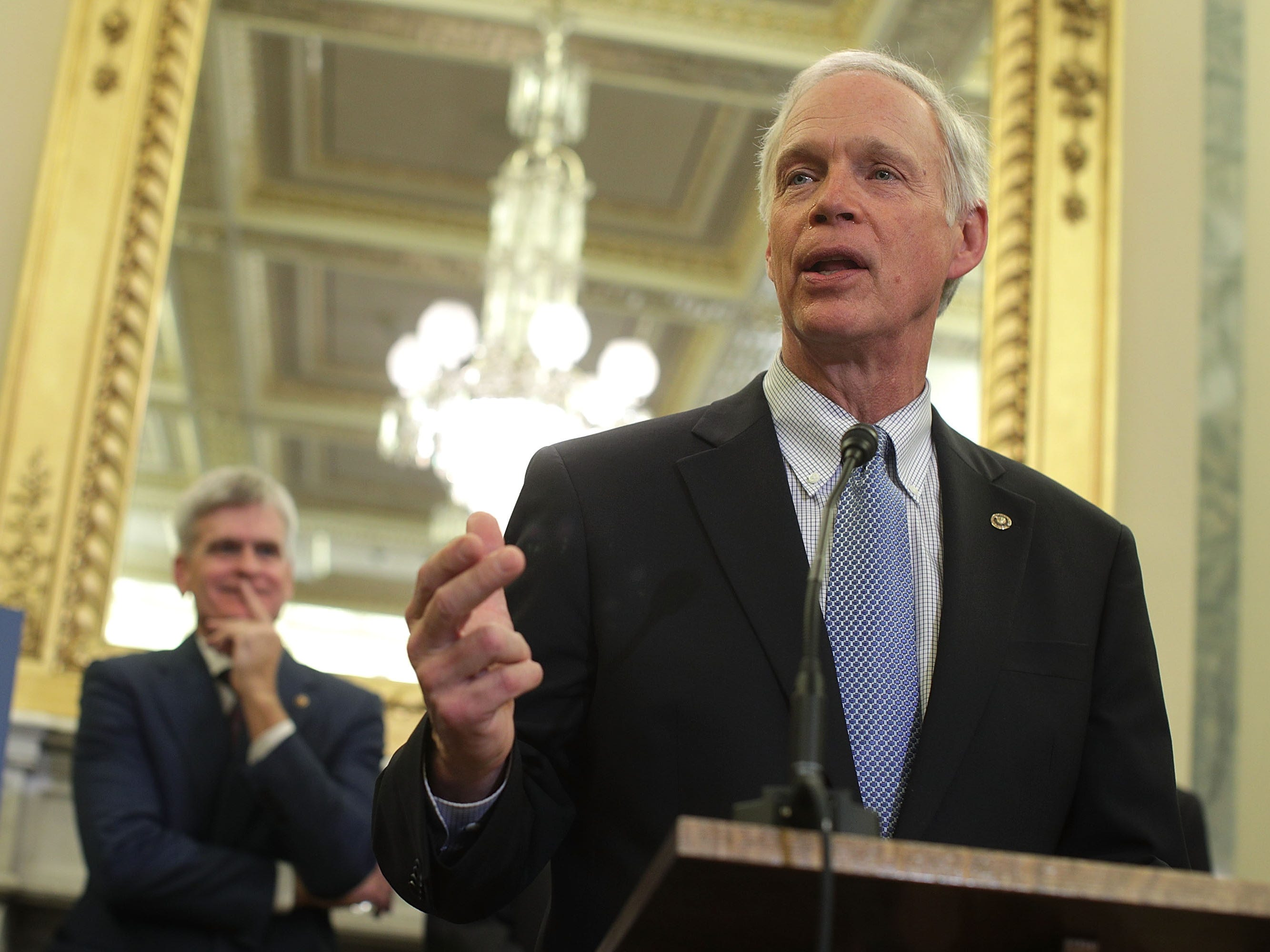 Sen. Ron Johnson (R-WI) (R) speaks as Sen. Bill Cassidy (R-LA) (L) listens during a news conference on health care on Capitol Hill in Washington.