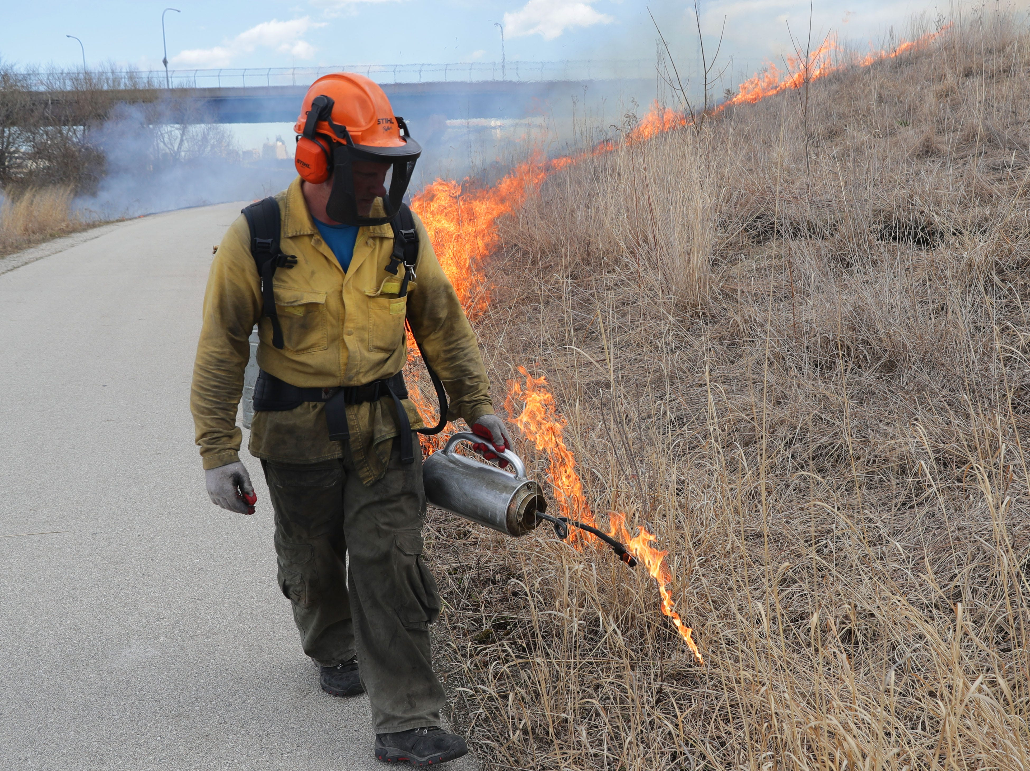 Chris Mann of Kettle Moraine Land Stewards LLC, uses a drip torch to conduct a controlled burn Tuesday at Three Bridges Park along the Hank Aaron Trail in the Menomonee Valley. The controlled burn, conducted by the Urban Ecology Center and Kettle Moraine Land Stewards, aids in the management of the land, allowing for healthy growth.