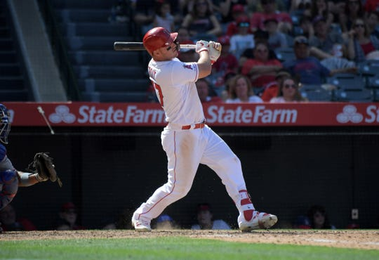 Angels centerfielder Mike Trout follows through on a two run home run Sunday against the Rangers.