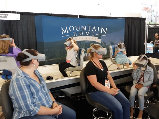Visitors to the 2019 Dallas Travel and Adventure show view a virtual reality video of the Twin Lakes Area at the Mountain Home Chamber of Commerce booth.