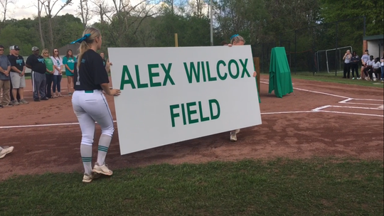 Brantley seniors Olivia Jones and Hannah Sims unveil the sign that marks the newly named Alex Wilcox Field.