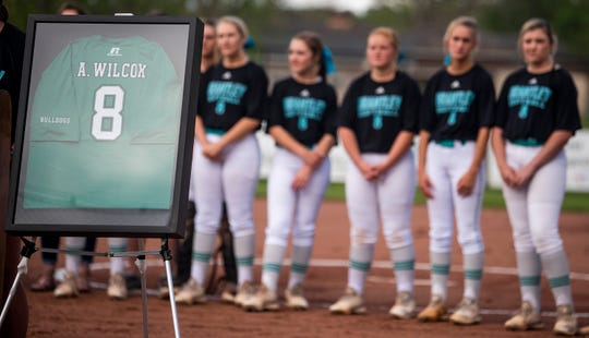 Brantley High School softball players look on as their field is named for former player Alex Wilcox (8) and her jersey is retired during a ceremony at the field in Brantley, Ala., on Tuesday April 9, 2019.