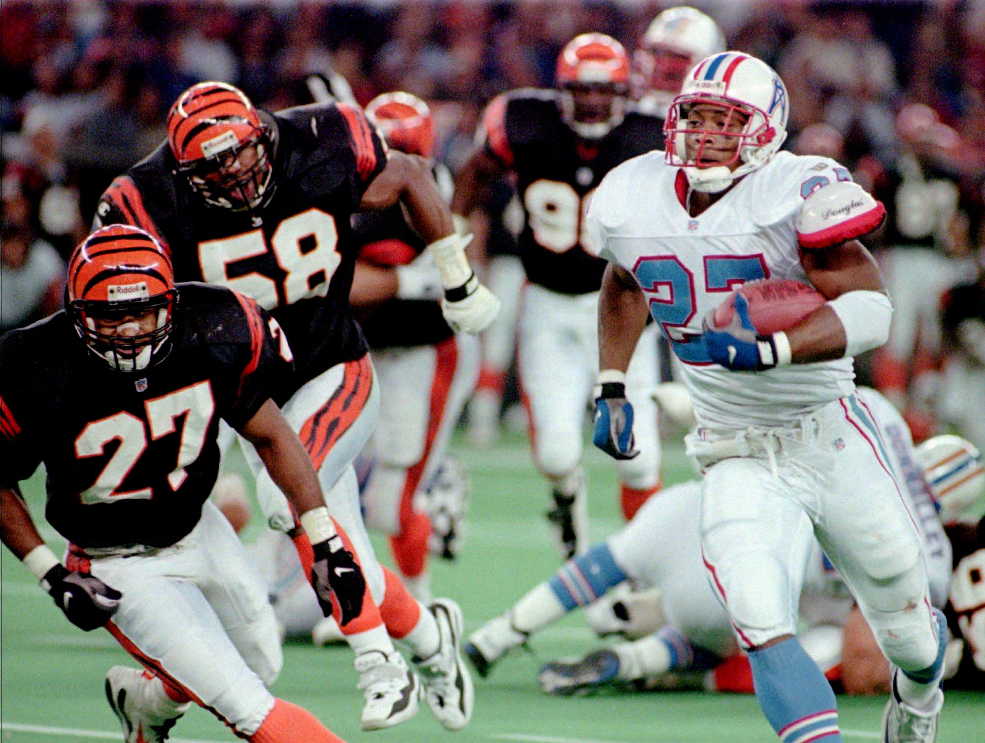 Houston Oilers running back Eddie George (27) is being pursues by Cincinnati Bengals defenders Bracey Walker (27) and Steve Tovar (58) on his way to a 45-yard touchdown run  Oct. 6, 1996 in Cincinnati. George gained 152 yards in the Oilers 30-27 win.