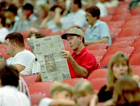 A Houston Oilers fan reads the paper as he waits for the game to start against the Baltimore Ravens Sept. 15, 1996 in Houston. The lame-duck Oilers hit a new low with a record-breaking 20,082 in attendance. The Oilers won 29-13.