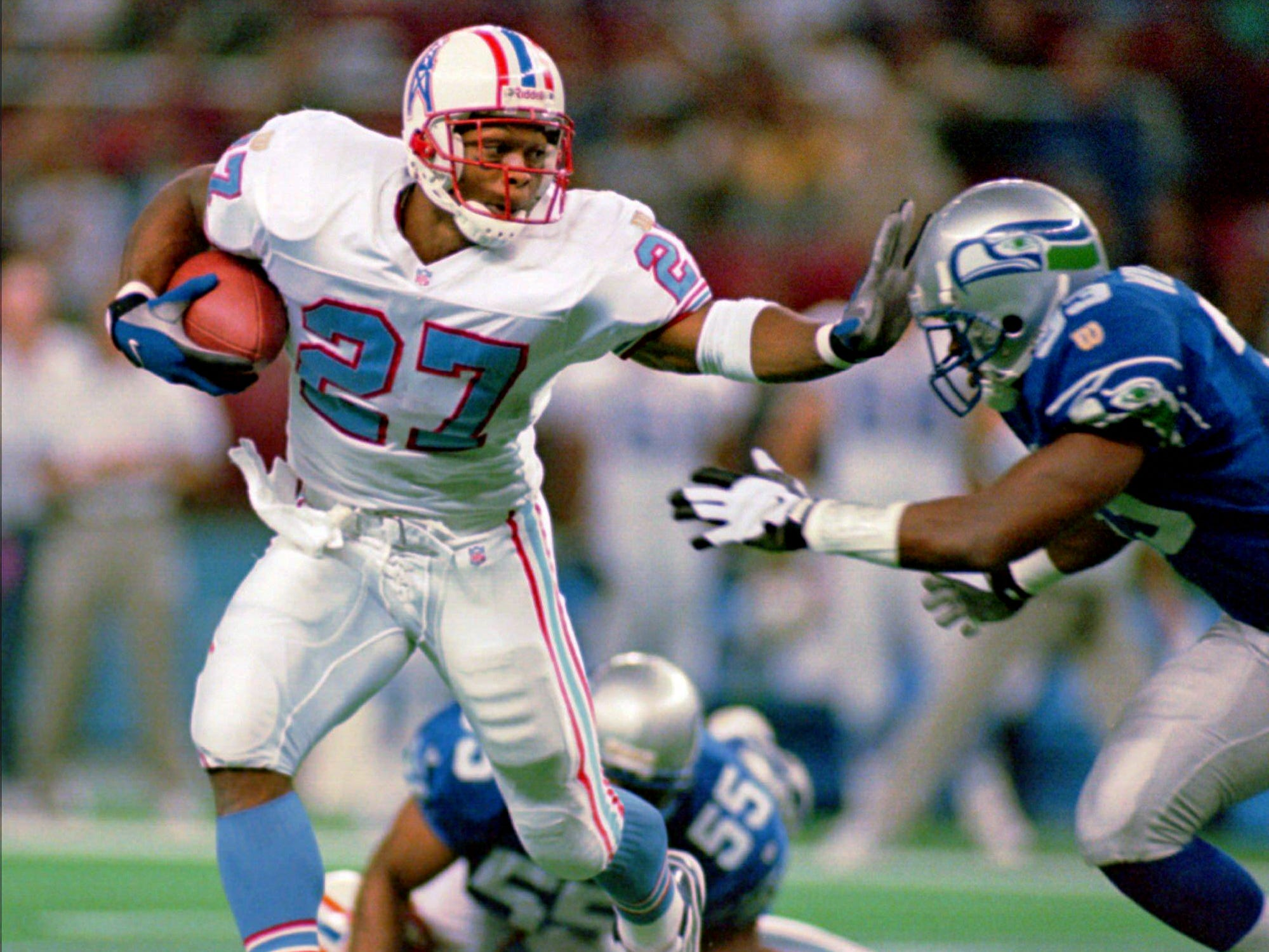 Houston Oilers running back Eddie George (27) holds off Seattle Seahawks defender Darryl Williams (33) in the first quarter of their Nov. 3, 1996 game in Seattle.