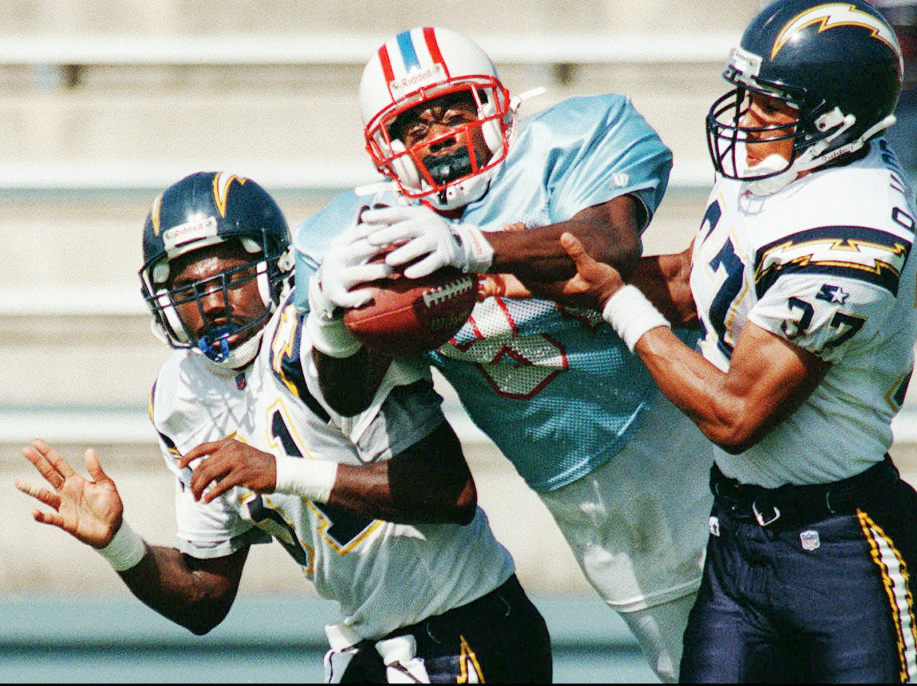 Houston Oilers receiver Chris Sanders is sandwiched by San Diego Charger defenders Willie Clark, left, and Rodney Harrison during morning practice at the Oilers training camp Aug. 16, 1995 at Trinity University in San Antonio.