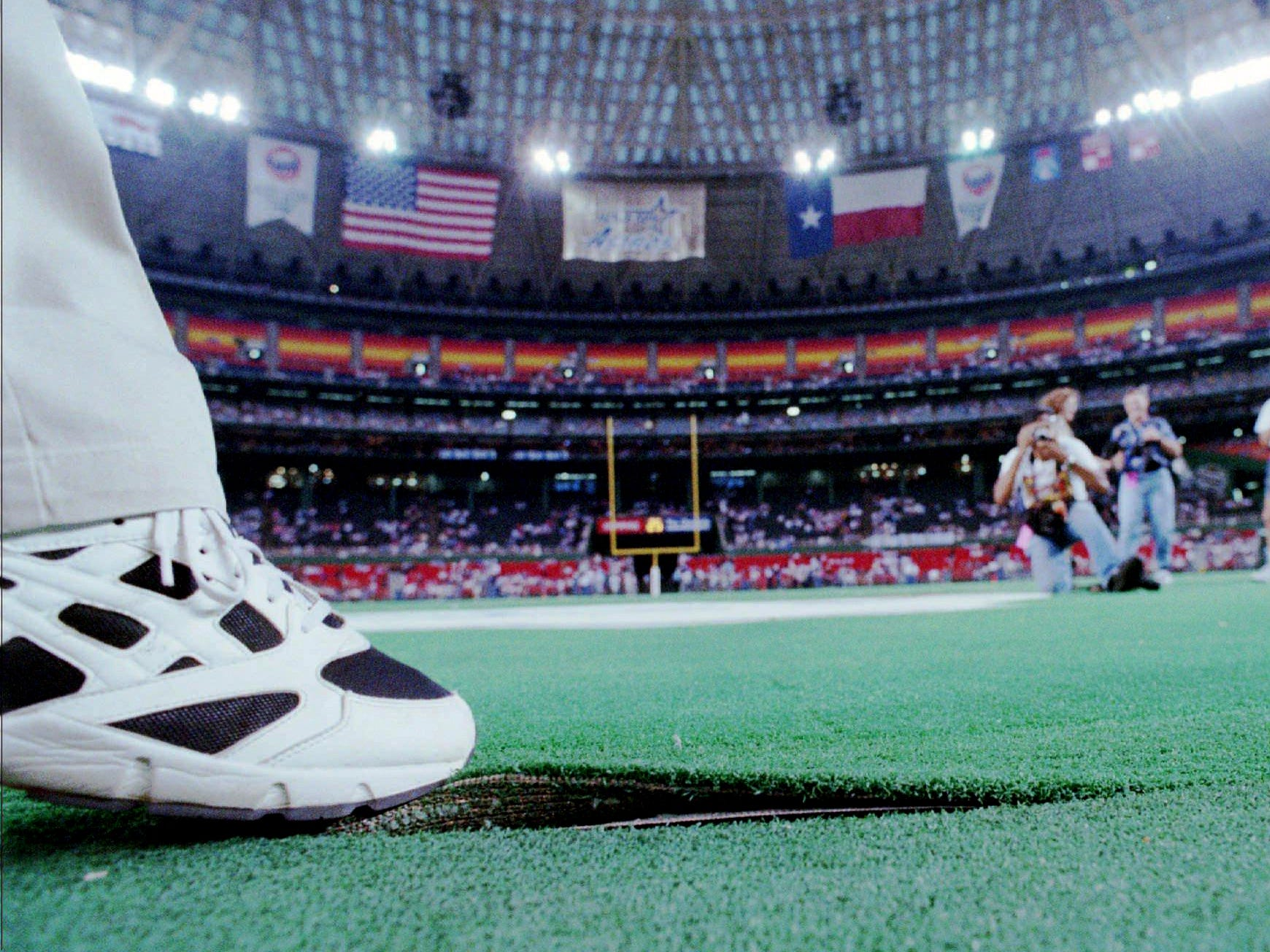 The toe of a local television commentator pulls up a portion of the artificial field in the Astrodome during a delay in the start of the Houston Oilers game with the San Diego Chargers in Houston Aug. 19, 1995. The game was canceled Saturday night because the artificial turf at the Astrodome was considered unsafe for play.