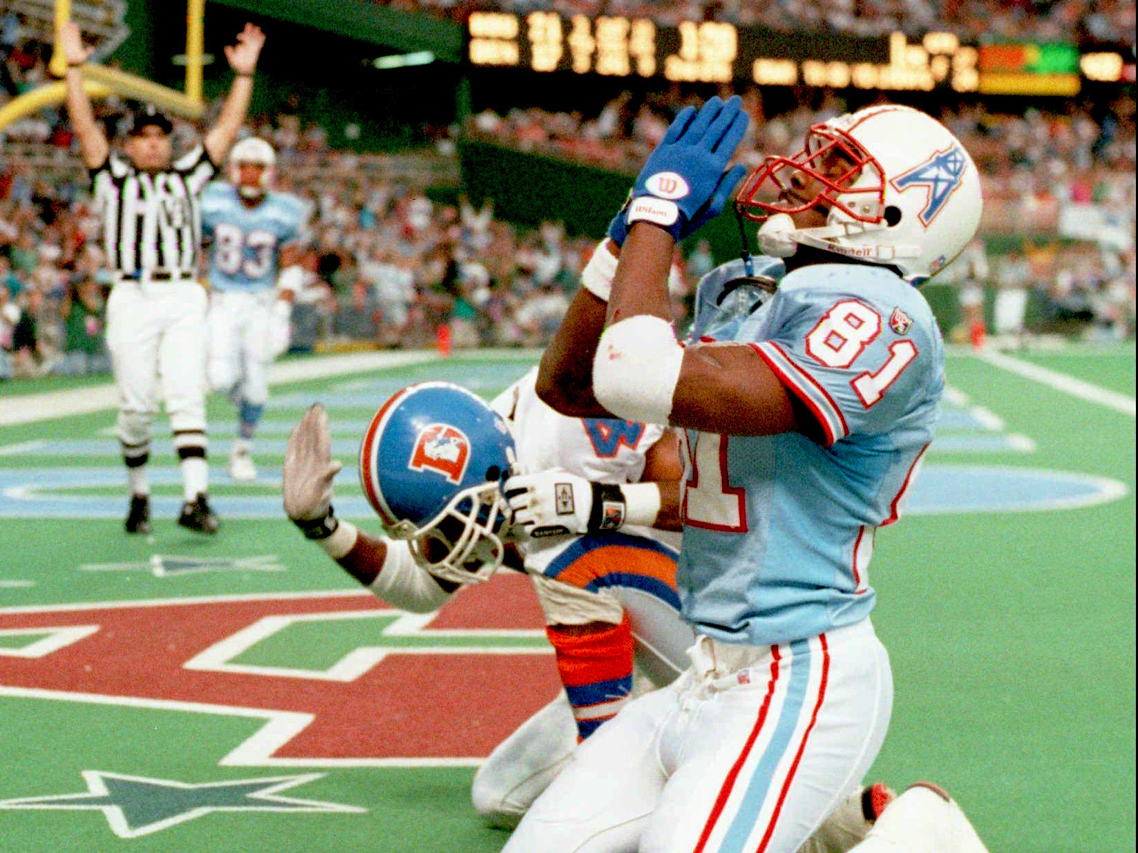 Houston Oilers Chris Sanders looks to the heavens in thanks after hauling in a 33-yard second quarter touchdown pass, beating Broncos' Lionel Washington, who pounds the turf behind Sanders Nov. 26, 1995 in Houston. The Oilers won 42-33.
