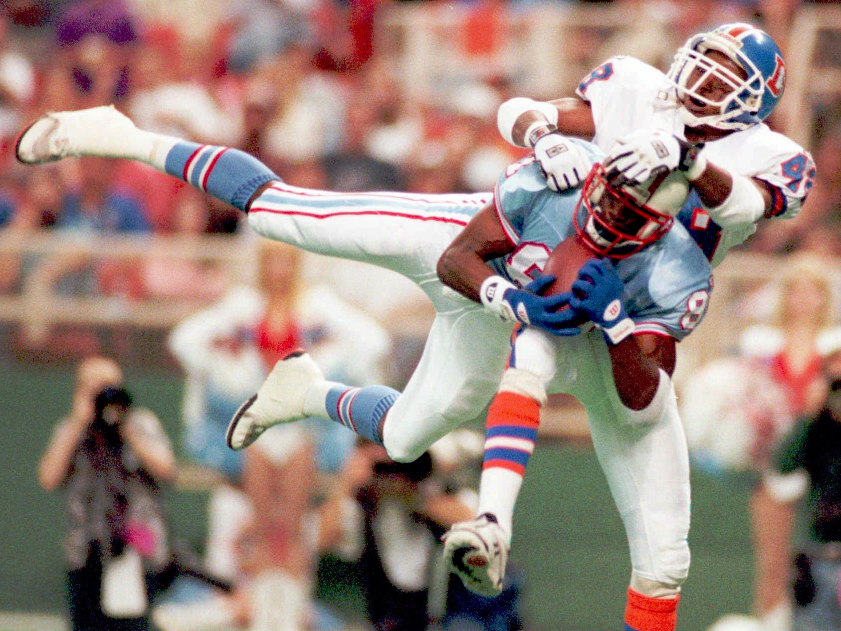 Houston Oilers receiver Chris Sanders hauls in a 36-yard first quarter touchdown pass from Chris Chandler, beating Broncos defensive back Lionel Washington Nov. 26, 1995 in Houston. The Oilers won 42-33.