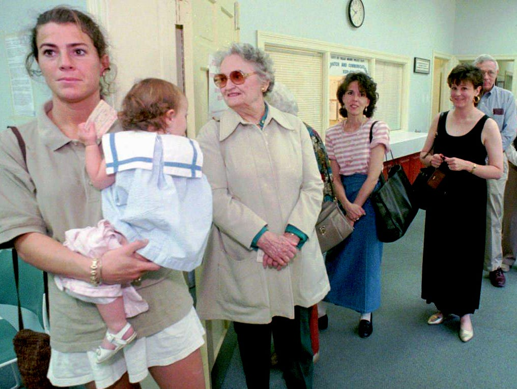 Jodie Smith, left, holds her daughter, Leila, as she and others line up for the last day of early voting on the Houston Oilers referendum in Nashville May 2, 1996. The regular election day for the vote is May 7.