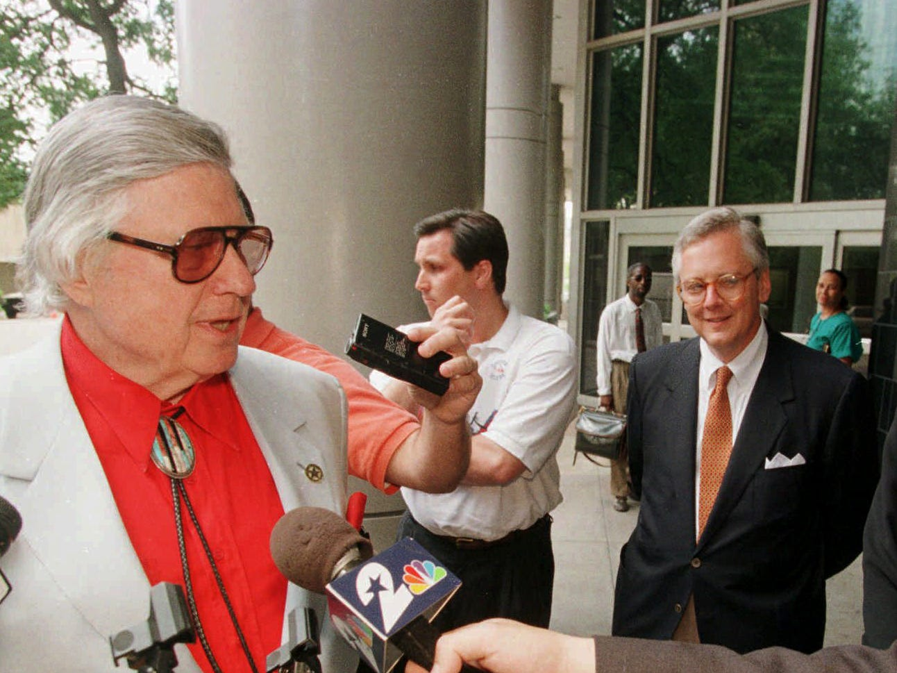 Houston Oilers owner Bud Adams, left, talks with reporters May 8, 1997 in Houston outside the federal courthouse after reaching an agreement, of undisclosed conditions, during mediation with Drayton McLane, Jr., owner of the Houston Astros and head of Astrodome USA, that releases the Oilers from their contract with the Astrodome and likely will allow the football team to play in Tennessee this fall. Smiling at right is federal mediator Alice Olive Parrott.