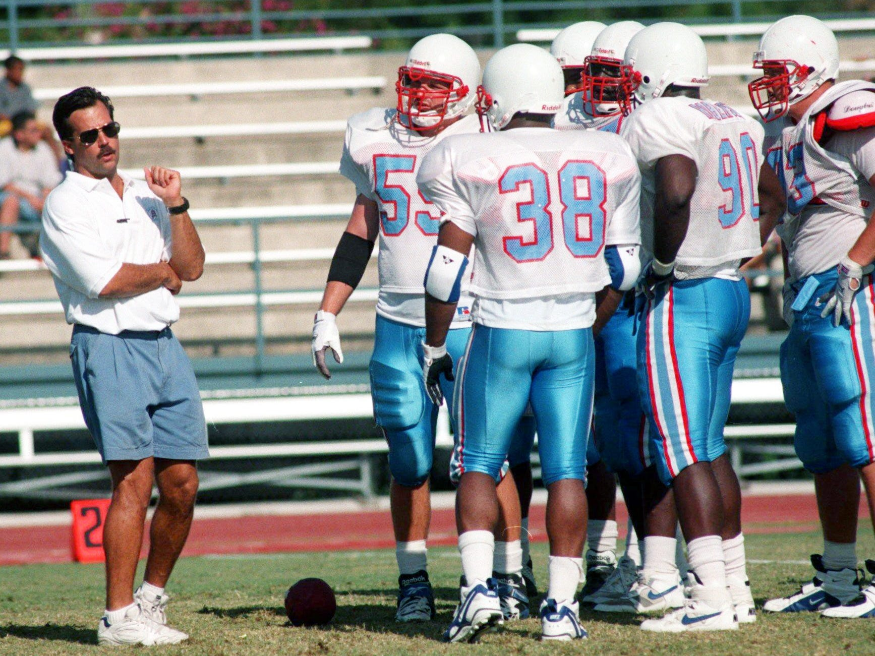 Houston Oilers head coach Jeff Fisher, left, talks with some of his players during a scrimmage on the field of Trinity University, home of their training camp in San Antonio, Texas July 26, 1996.