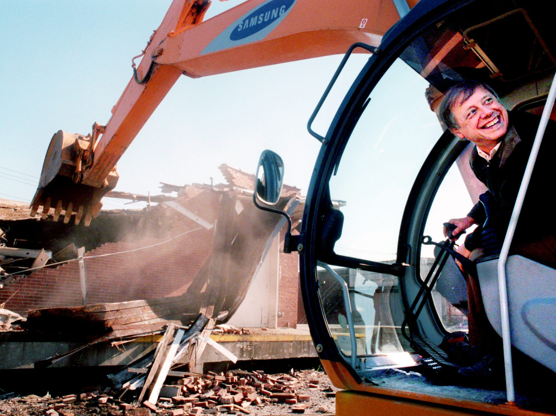 Metro Mayor Phil Bredesen smiles while demolishing the old Jamison building with a front end loader to begin the first building demolition to clear the way for the new stadium Nov. 27, 1996.