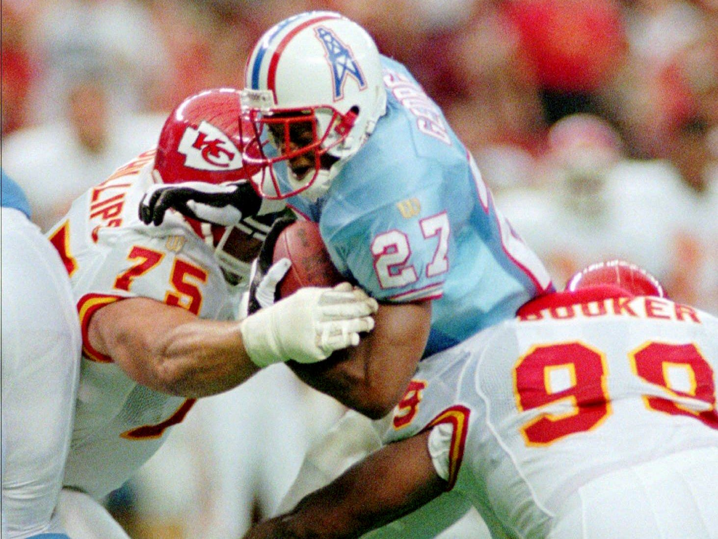 Kansas City Chiefs' Joe Phillips (75) and Vaughn Booker (99) stop Houston Oilers running back Eddie George (27) during the second quarter Sept. 1, 1996 in Houston. The Chiefs beat the Oilers 20-19.