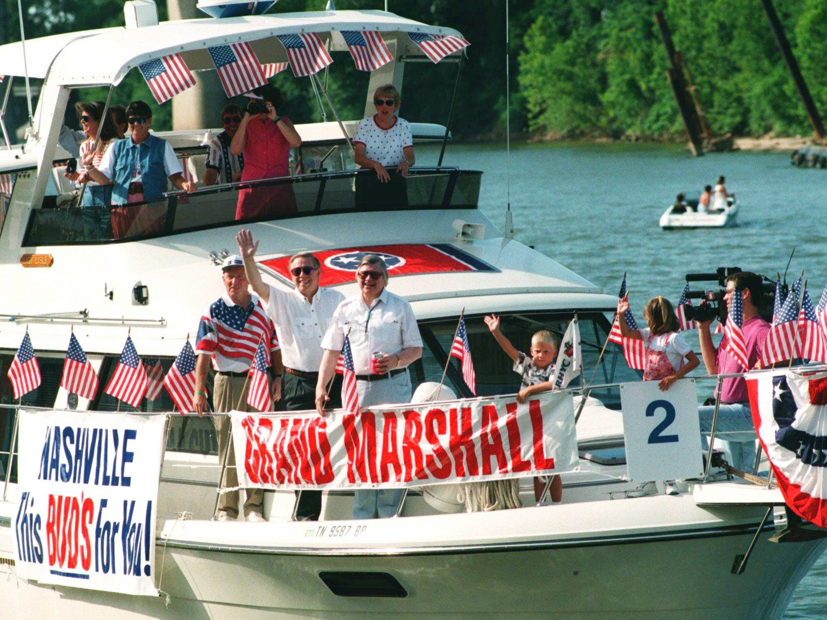 Metro Mayor Phil Bredesen and grand marshal Houston Oilers owner Bud Adams, center, greet the crowd at Riverfront Park during the boat parade for the 4th of July holidays downtown Nashville July 4, 1996.